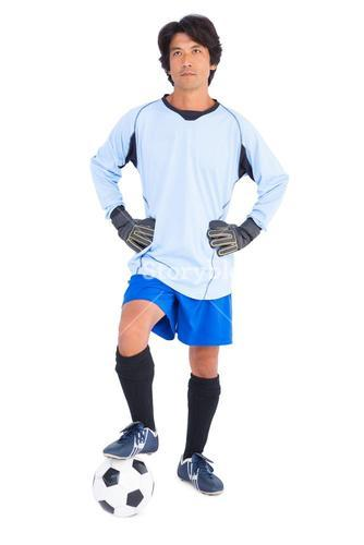 Goalkeeper in blue holding ball with foot