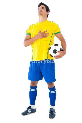 Football player in yellow with ball listening to anthem