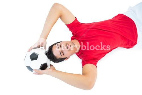 Football player in red lying with ball