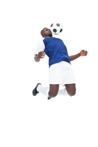 Football player in blue jersey controlling ball