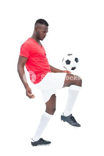 Football player in red jersey controlling ball