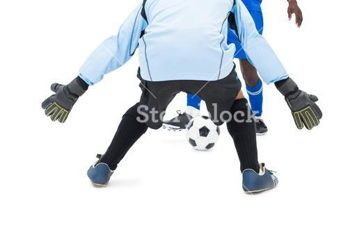 Striker hitting football at goalkeeper
