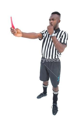 Serious referee showing red card blowing whistle