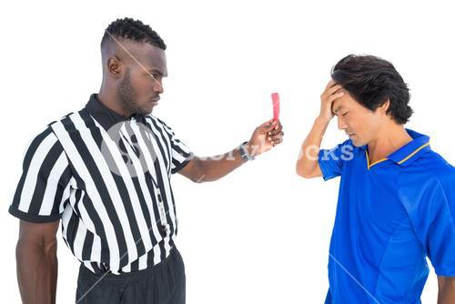 Serious referee showing red card to player