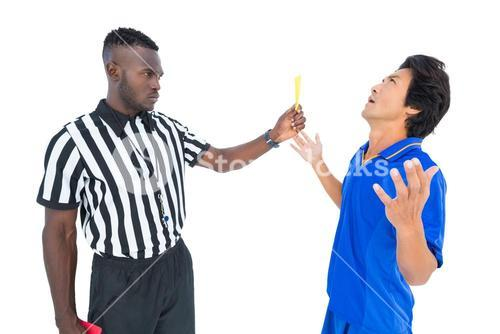 Serious referee showing yellow card to player