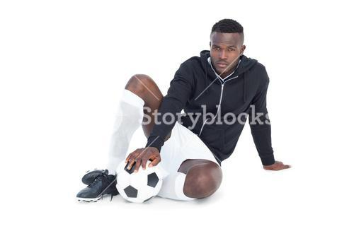 Football player sitting with ball
