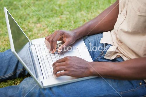 Man relaxing in his garden using laptop