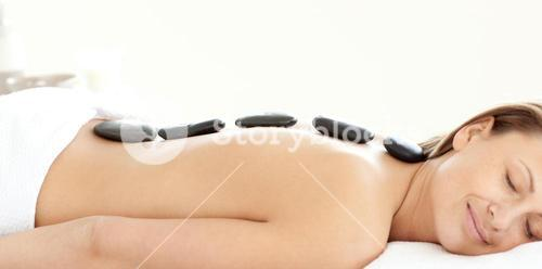 Charming woman with hot stones on her back