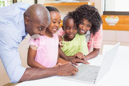 Cute siblings using laptop together with parents