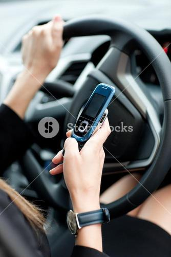 Close up of a businesswoman sending a text while driving