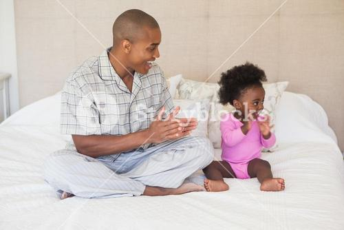 Father and baby girl sitting on bed together
