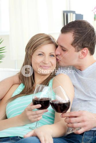 Portrait of an affectionate young couple drinking red wine