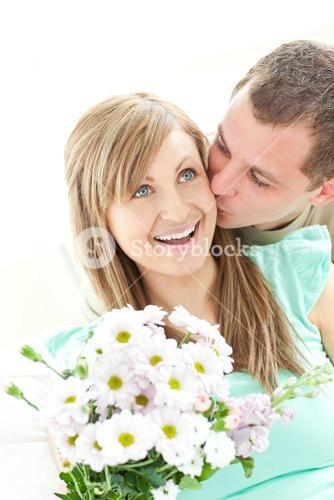 Attentive man giving a bunch of flowers to his girlfriend