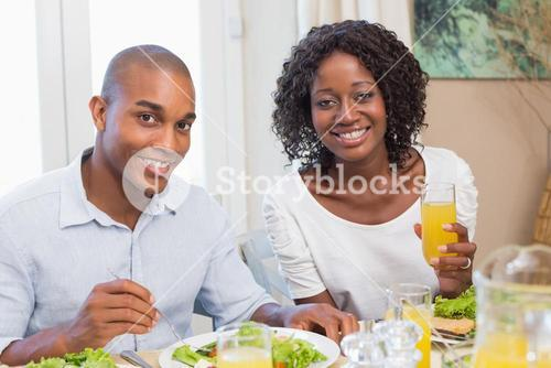 Couple enjoying a healthy meal together smiling at camera