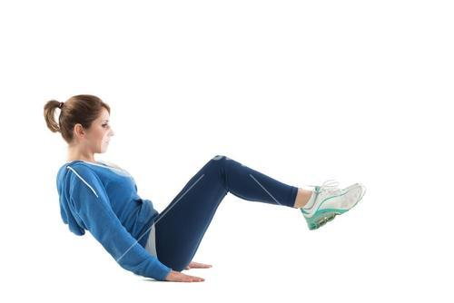 Side view of woman in core balance pilates pose