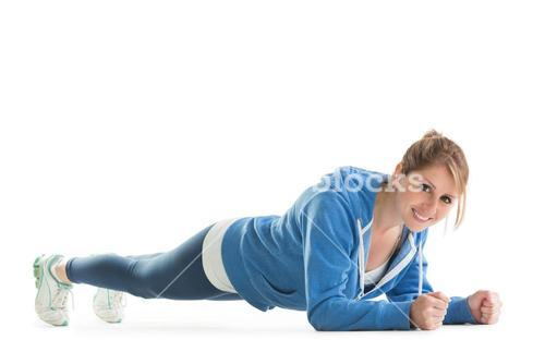 Smiling young woman in basic plank posture