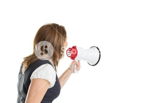 Young businesswoman shouting into bullhorn