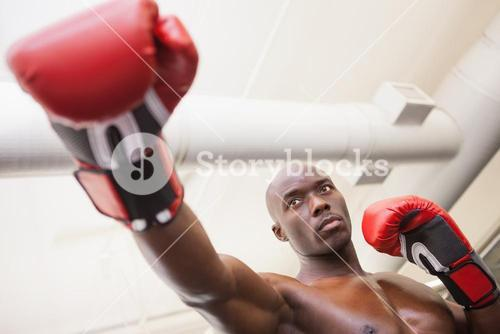 Male boxer attacking with his right in health club
