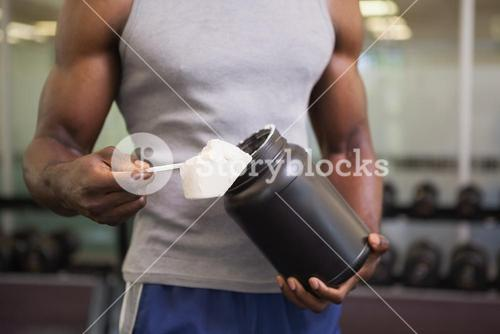 Body builder holding a scoop of protein mix in gym