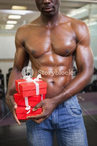 Mid section of a muscular man with gift boxes
