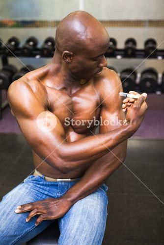 Muscular man injecting steroids