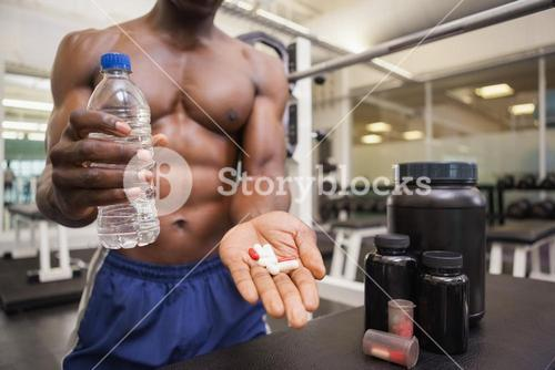 Shirtless muscular man holding vitamin pills