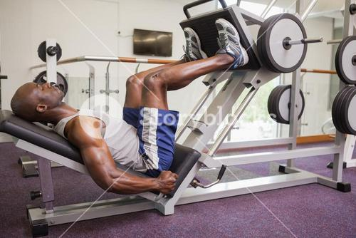 Male weightlifter doing leg presses in gym