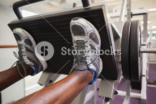 Weightlifter doing leg presses in gym