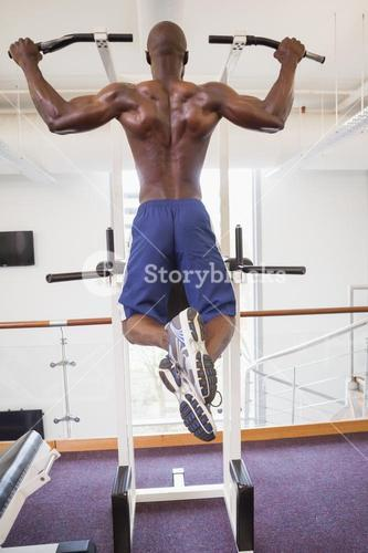 Male body builder doing pull ups at gym