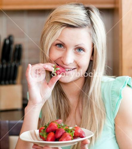 Delighted woman eating fruits