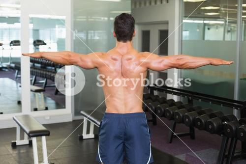 Bodybuilder with arms outstretched in gym
