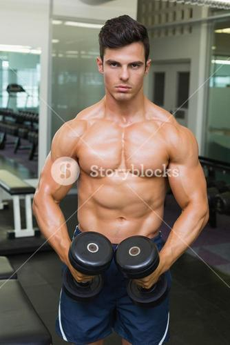 Shirtless muscular man flexing muscles with dumbbells in gym