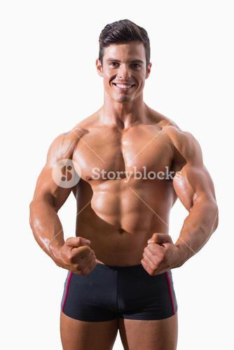 Portrait of a muscular young man clenching fists