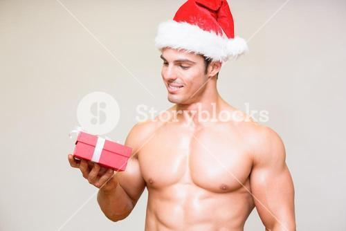 Macho man in santa hat holding gift over white background