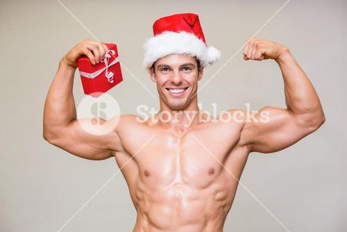 Portrait of shirtless macho man in santa hat holding gift
