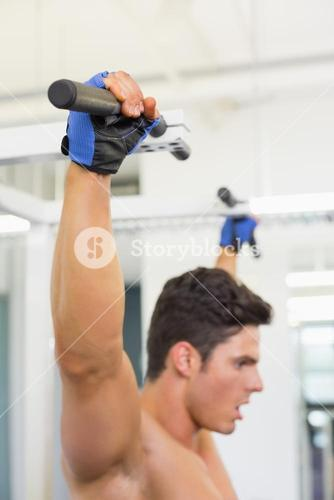 Side view of a shirtless male body builder doing pull ups