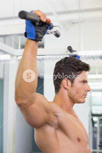Shirtless male body builder doing pull ups at the gym