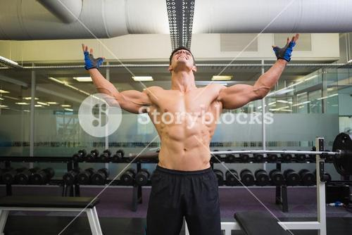 Bodybuilder with arms raised in gym