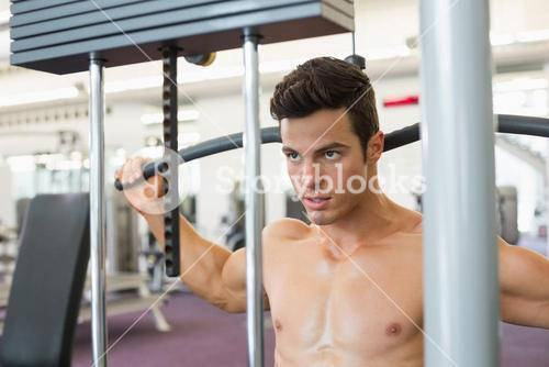 Muscular man exercising on a lat machine in gym