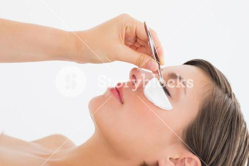 Close-up side view of hand plucking eyelashes