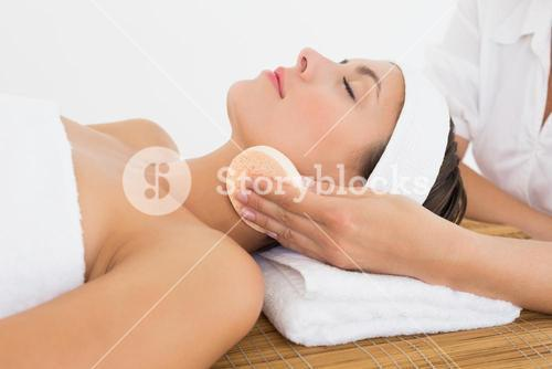 Hand cleaning womans face with cotton swabs