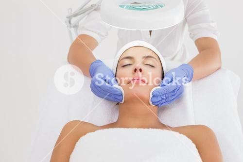 Hands cleaning womans face with cotton swabs