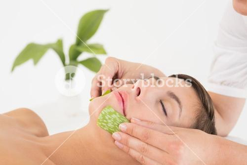 Attractive woman receiving aloe vera massage at spa center