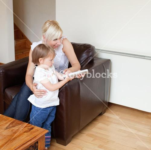 Girl holding a remote control standing in the living room