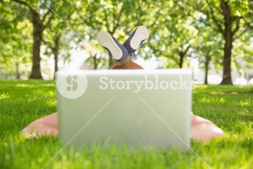 Redhead using laptop in the park