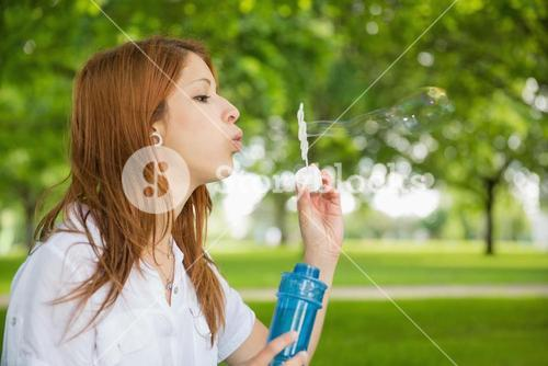 Pretty redhead blowing bubbles in the park