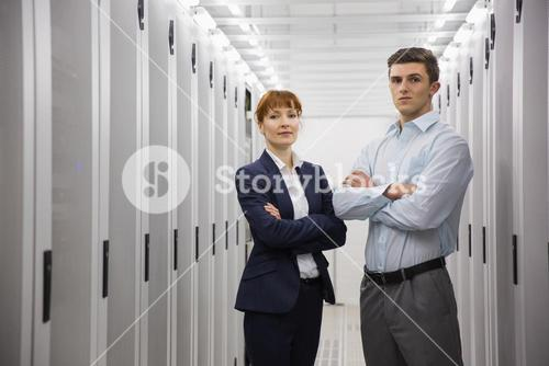 Team of computer technicians looking at camera