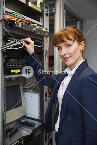 Pretty computer technician smiling at camera while fixing server