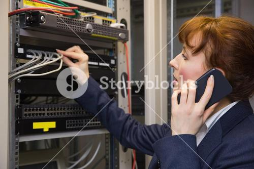 Pretty computer technician talking on phone while fixing server