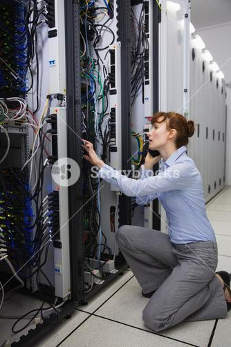 Serious technician talking on phone while analysing server